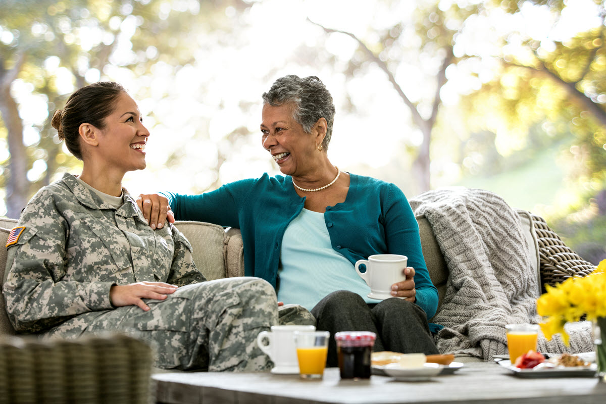 military member and mother sitting and smiling