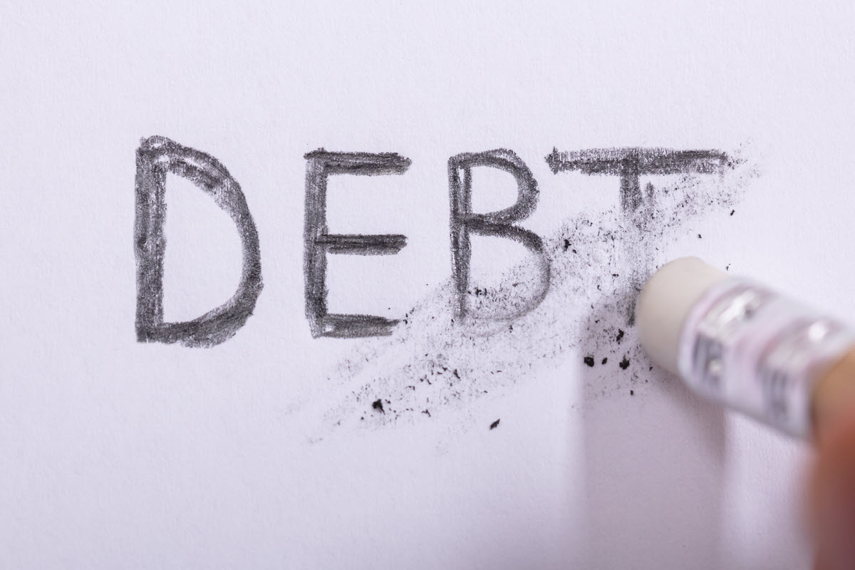 eraser erasing the word debt on paper