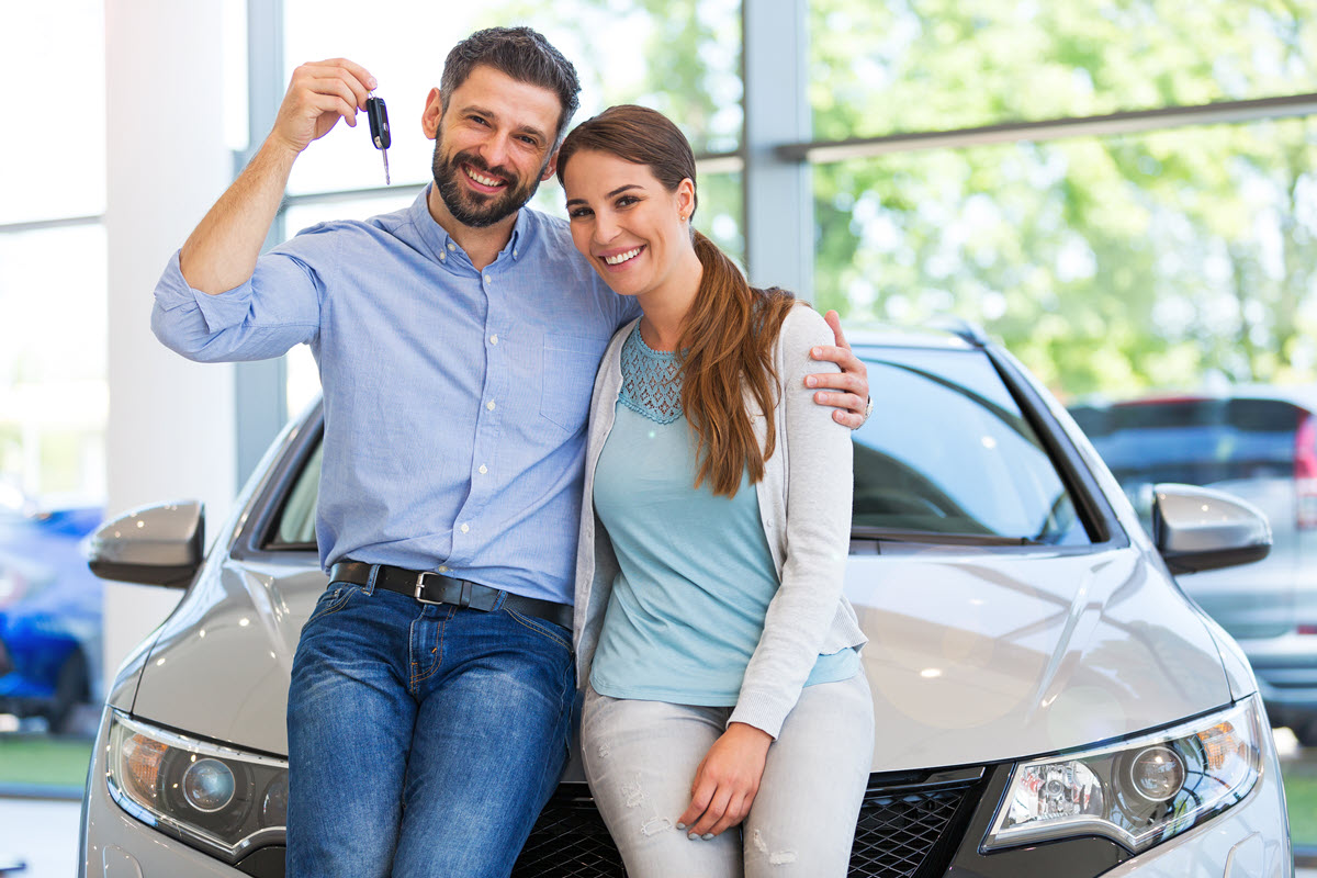 couple holding keys to a car leaning on a car