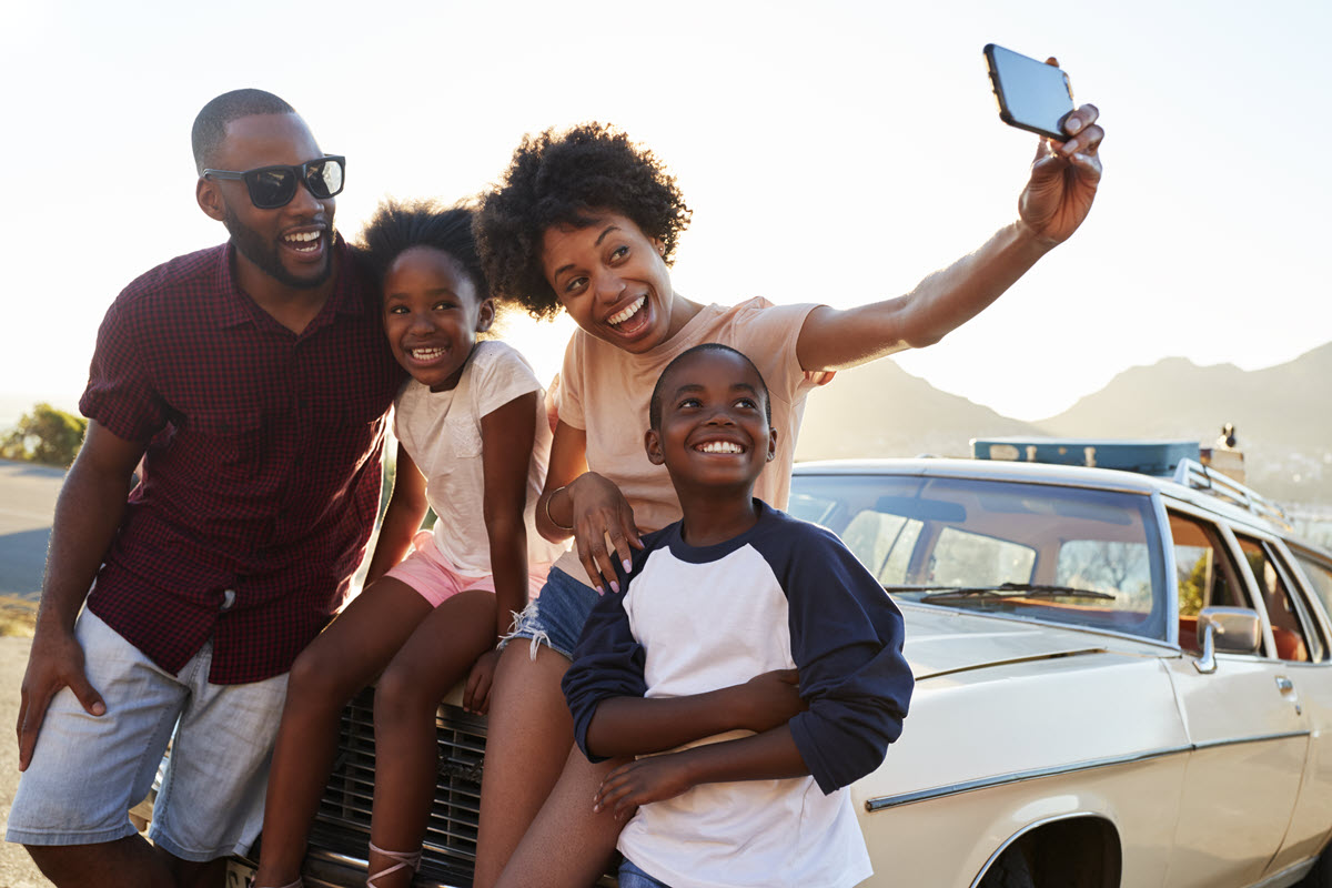 smiling family taking a selfie on a car