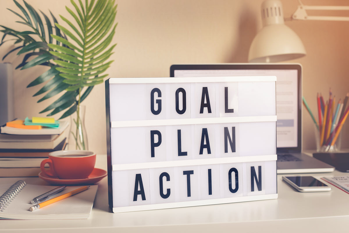 goal plan action sign on a desk
