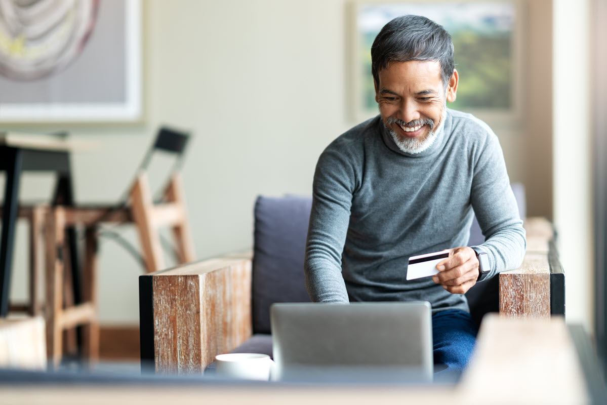 older man in front of computer with credit card